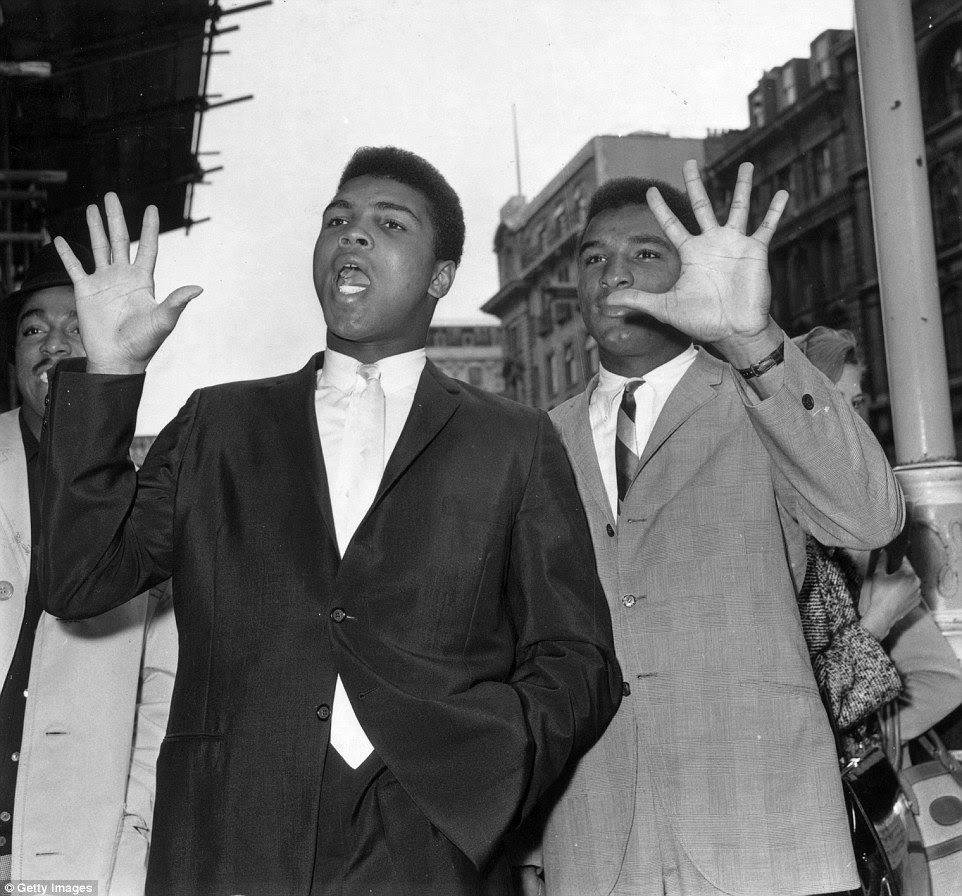 Ali (left) waves to the crowds in June 1963 as he walks along with the street with his brother Rudolph, later known as Rahman Ali