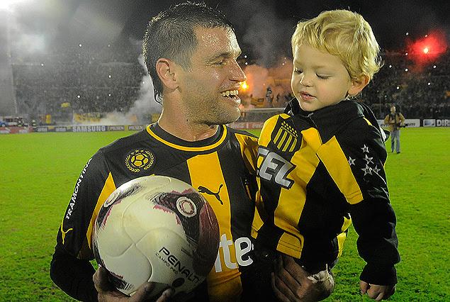 Antonio Pacheco con su hijo Benjamín en brazos y la pelota que se llevó por los tres goles y que seguramente tendrá lugar preponderante en su vitrina.