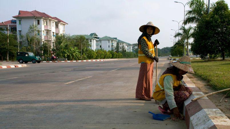 Des femmmes balayent la route dans un quartier résidentiel pour les fonctionnaires de l'État birman. Ce  sont parfois les seuls piétons que l'on croise dans la journée dans les rues de la capitale birmane.