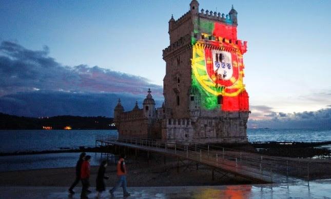 A Torre de Belém, em Lisboa, iluminada com as cores e o brasão português  (Foto: Reuters )