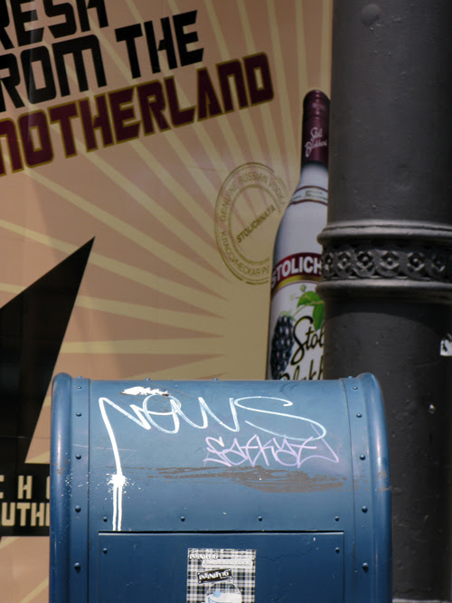 graffiti on a mailbox with Stoli vodka ad and a pillar in the background, Manhattan, NYC