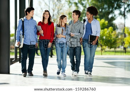 Full length of happy college students walking together on campus