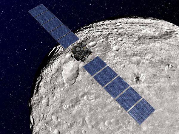An artist's concept of the Dawn spacecraft orbiting asteroid Vesta.