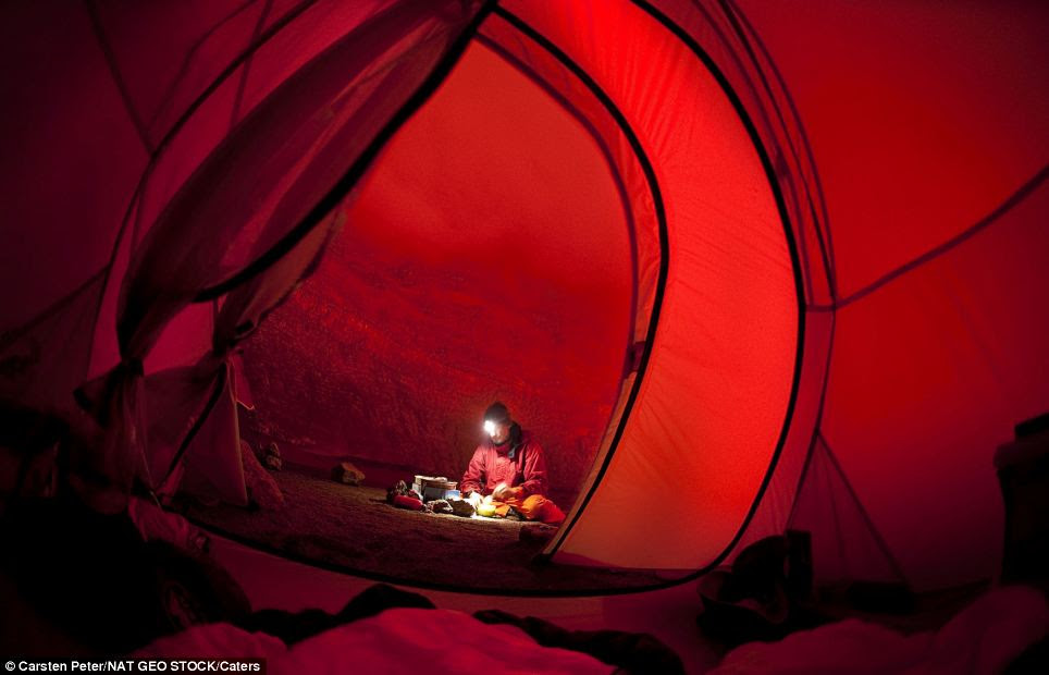 A picture taken by Carsten Peter from inside his tent as a man cooks a meal outside in Nyiragongo volcano in Congo