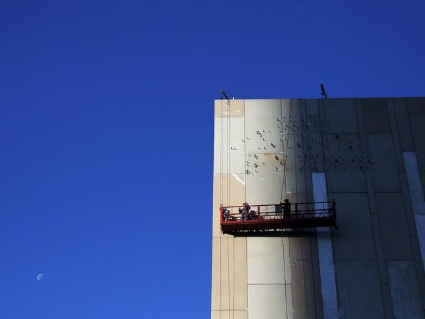 Operários trabalham em prédio em construção em dia de céu limpo em Pequim nesta quarta-feira (2) (Foto: Damir Sagolj/Reuters)