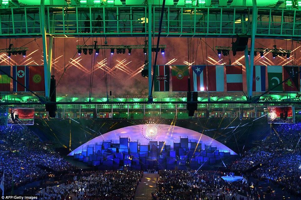 Fogos de artifício explodem sobre a pira olímpica com a chama olímpica durante a cerimônia de abertura