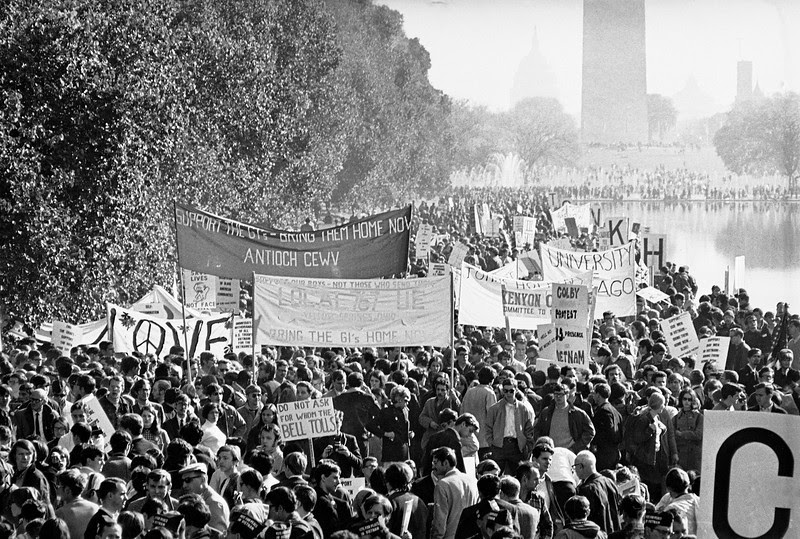 Description of  Anti-war demonstrators gather opposite the Lincoln Memorial in Washington, D.C., Oct. 21, 1967.  In the background is the Reflecting Pool, the base of the Washington Monument, and barely visible through the haze is the Capitol Building.  (AP Photo)