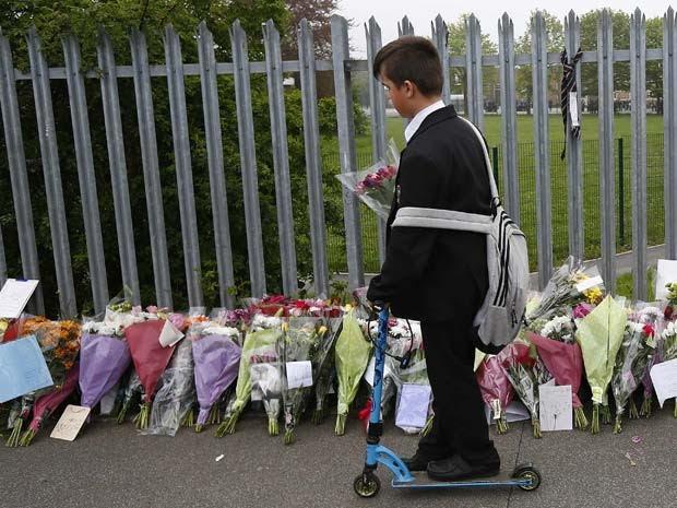Aluno deixa flor em grade da escola em tributo a professora Anne Maguire, morta por estaudante do Corpus Christi Catholic College em Leeds (Foto: REUTERS/Darren Staples)