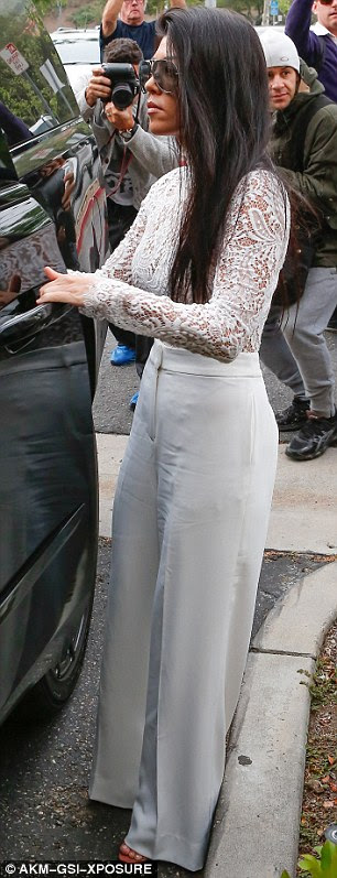 She's got the white stuff: Kourtney coordinated with her little sister, but flashed her bra in a lace top