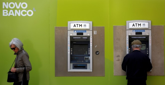 Dos ciudadanos pasan delante de una oficina de Novo Banco en Lisboa, Portugal.REUTERS/Pedro Nunes