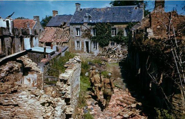 Tentara Amerika Serikat mencari di antara rumah-rumah runtuh di barat Prancis setelah D-Day. (Frank Scherschel—Time & Life Pictures/Getty Images)