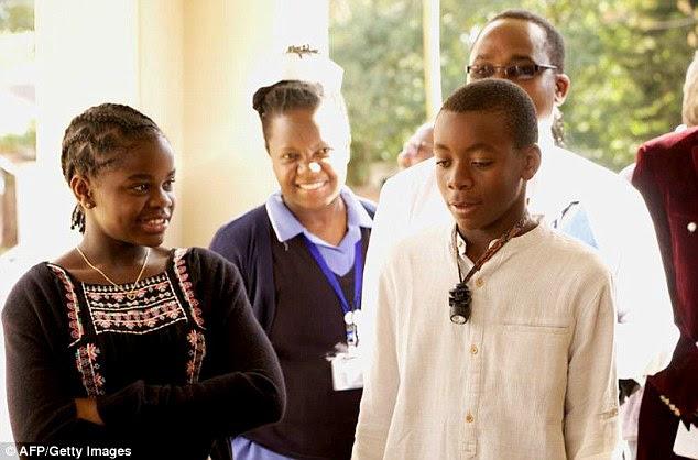 Os filhos adotivos de Madonna, David Banda (à direita) e Mercy James (à esquerda), ficam durante a inspeção de uma unidade cirúrgica de 50 leitos para crianças que sua instituição de caridade, Raising Malawi em julho