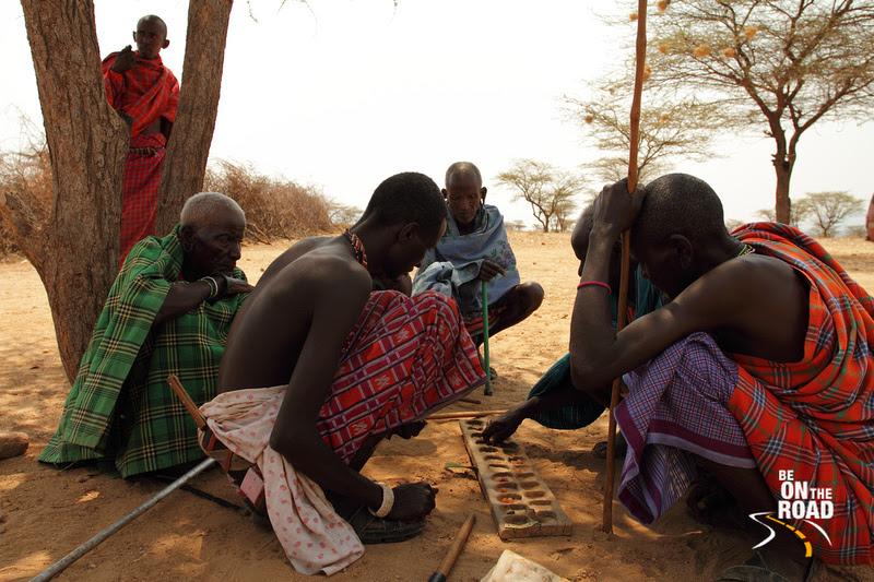 Samburu Elders huddle together under a tree to play a game