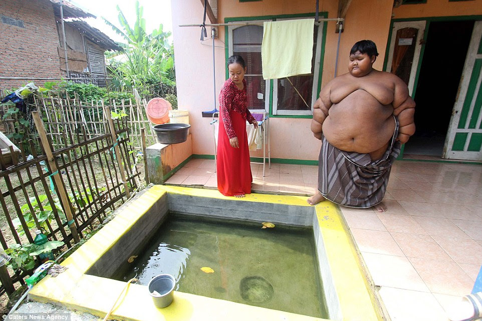 Arya Permana (pictured with his mother), named the world's fattest child, weighs an eye-watering 192 kilograms and has been forced to wear just a sarong as normal clothes do not fit him