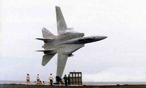 An F-14 Tomcat does an extremely close flyby of the nuclear-powered aircraft carrier, USS Stennis.