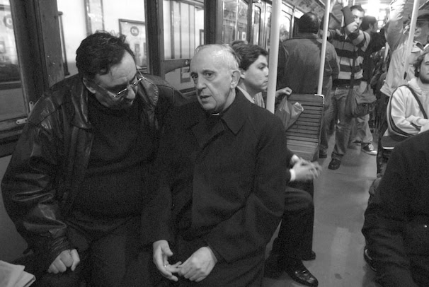 "An undated handout photo released on 14 March 2013 by Ediciones B editorial from the book 'The Jesuit: history of Francis, the Argentinian Pope"" by Sergio Rubin and Francesca Ambrogetti shows Jorge Mario Bergoglio (C) speaking with a passanger during a travel in metro in Buenos Aires, Argentina."