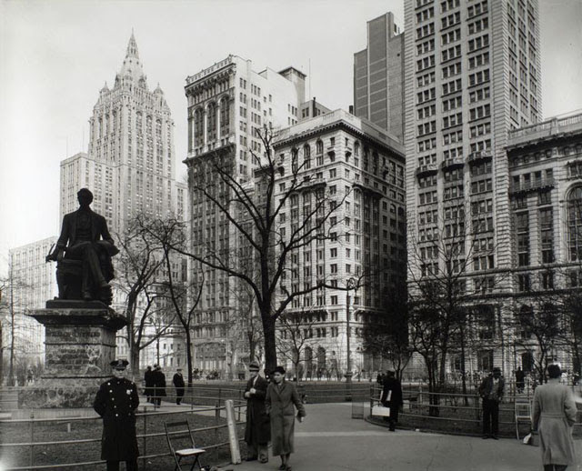 Madison Square, looking northeast, Manhattan. Policeman stands in front of Seward statue, shoe-shine man lounges on railing, right, Metropolitan Life building rises above park.