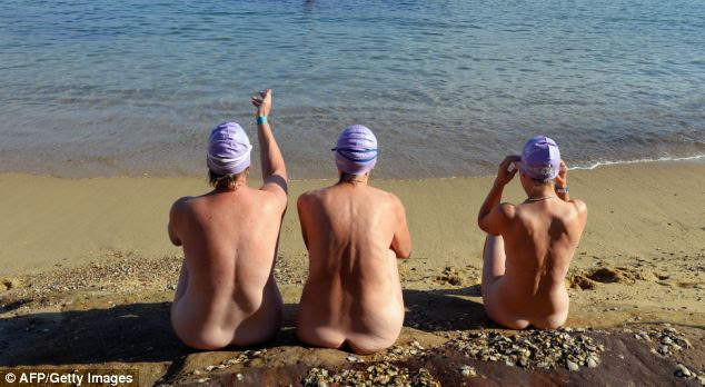 Three competitors wait for the start of the swim clad in nothing but swimming caps
