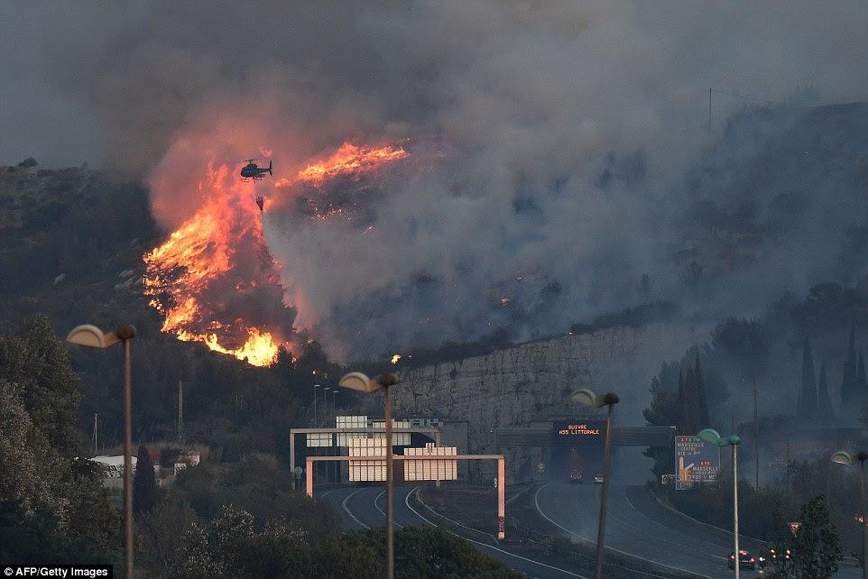 Um incêndio sprays helicóptero extinção de produtos químicos em uma encosta queimando perto de Marselha.  Os incêndios são os piores na área há décadas