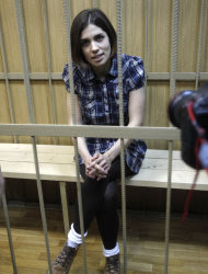 """Nadezhda Tolokonnikova, a member of the feminist punk band, Pussy Riot, sits behind bars in Moscow's Tagansky district court, Wednesday, June 20, 2012. She and two other band members face up to seven years on hooliganism charges after their February """"punk prayer"""" at Moscow's Christ the Savior Cathedral in which they asked Holy Mary to deliver Russia from President Vladimir Putin.(AP Photo/Misha Japaridze)"""