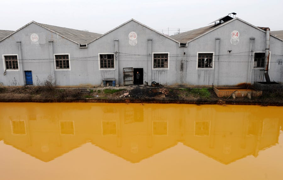 A manufacturer of screws and nuts is situated next to a polluted river in Jiaxing, Zhejiang province.
