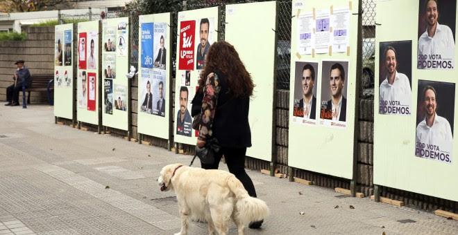 Una mujer pasa por delante de carteles electorales de los distintos candidatos a Presidente de Gobierno para las elecciones generales del próximo domingo en Santurce (Vizcaya), durante la campaña electoral para las elecciones generales del próximo 20-D. E