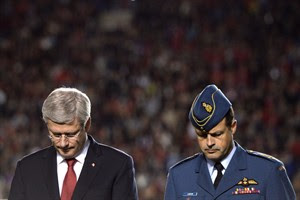 Prime Minister Stephen Harper, left, and General Thomas Lawson, Chief of the Defence Staff, participate in a tribute to the Canadian Forces, as well as fallen heroes, Corporal Nathan Cirillo and Warrant Officer Patrice Vincent, before the start of CFL action between the Ottawa Redblacks and the Montreal Alouettes in Ottawa on Friday Oct. 24, 2014. THE CANADIAN PRESS/Sean Kilpatrick