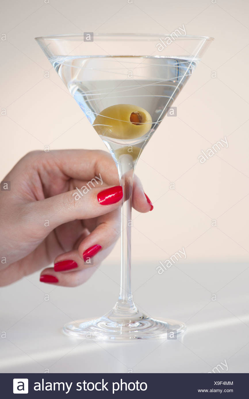 Close Up Of Womans Hand With Nail Polish Holding Martini Glass With