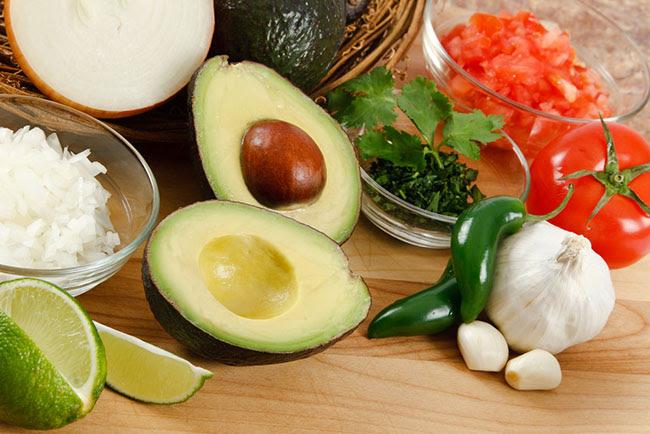 ingredientes para preparar guacamole en casa sobre una mesa de madera