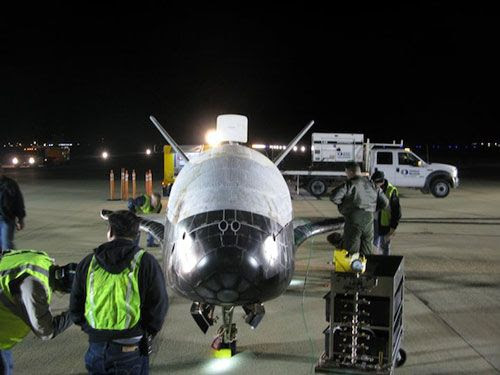Military personnel at Vandenberg Air Force Base, California, conduct a post-landing checkout on the OTV after its return home from space on December 3, 2010.