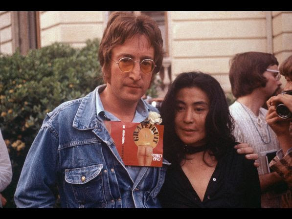 "John Lennon and his wife Yoko Ono are seen at the Cannes Film Festival, May 18, 1971. Lennon carries Ono's art book ""Grapefruit"" in his jacket."
