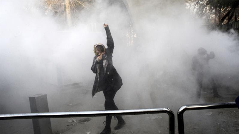 A university student attends a protest inside Tehran University while a smoke grenade is thrown by anti-riot Iranian police on December 30, 2017 [AP]