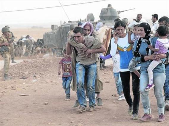 Refugiats kurds sirians travessen la frontera i entren a Turquia, dissabte.