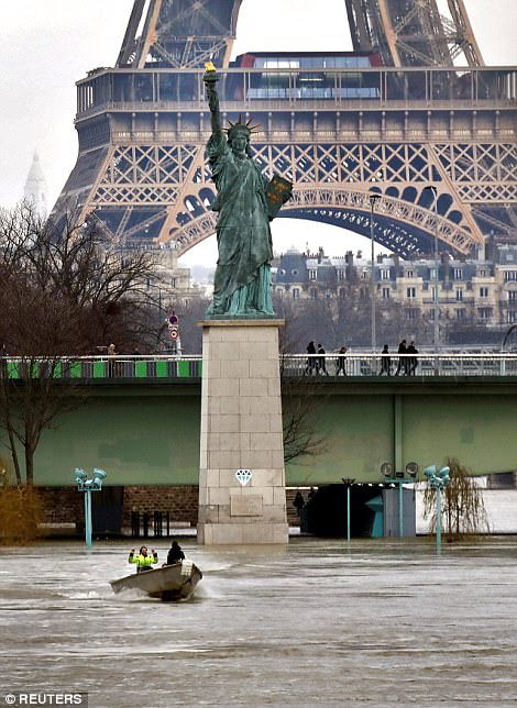 Leaks started to appear in some basements in Paris on Friday, while some residents on the city's outskirts were forced to travel by boat through waterlogged streets. Pictured: The Eiffel tower and replica of the Statue of Liberty shown near the swollen Seine in Paris