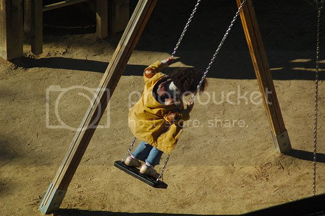 Kid standing on swing, Barcelona [enlarge]