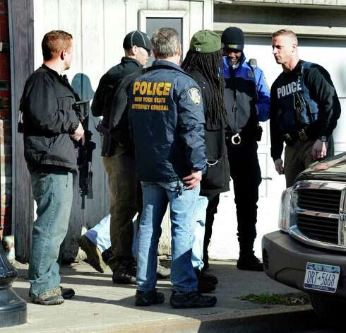 Members of the NYS Attorney Generals investigative unit along with members of the Albany Police Department take Gilbert Pilet in to custody on Henry Johnson Boulevard in Albany, N.Y. March 27, 2012.    (Skip Dickstein / Times Union) Photo: SKIP DICKSTEIN / 00016971A
