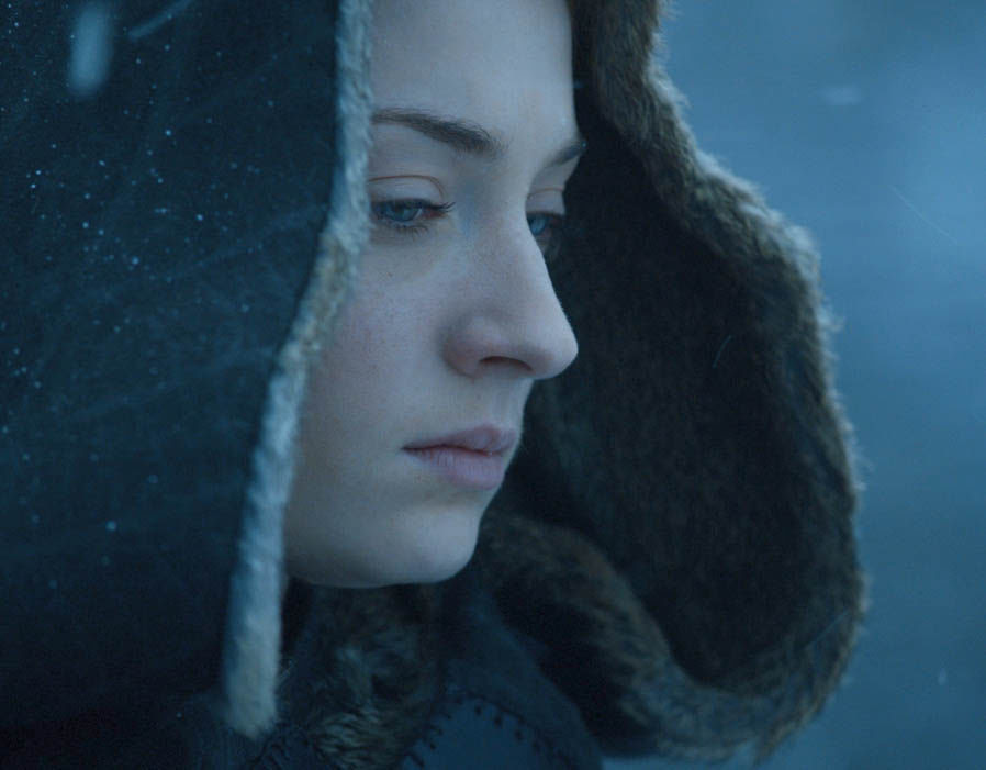 Sansa Stark appears to be putting the hood up on her cloak and making some sort of journey