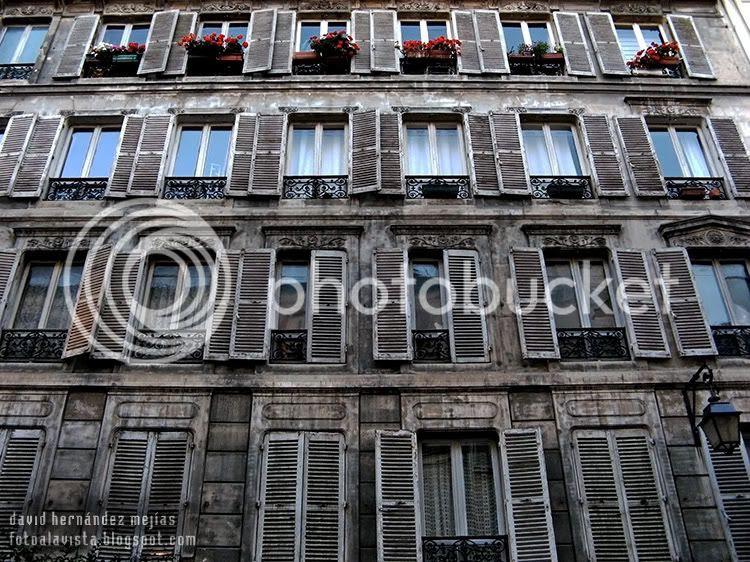Balconada de una casa de París con contraventanas mayoritariamente abiertas, recordando el anuncio del perfume Égoïste
