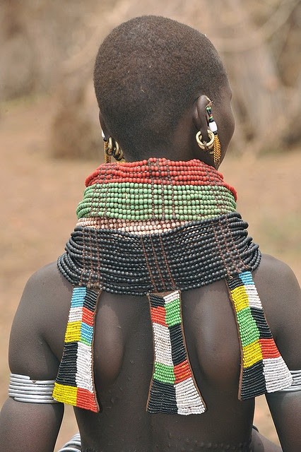 Africa | Nyangatom girl with nyeboli ornaments on the back of the necklace. The land of the Nyangatom is traditionally around Mount Naita, so they live just north of the disputed Ilemi triangle, currently held by Kenya in both South Sudan and Ethiopia. | ©World Discoverer