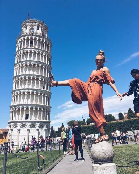 1 - Girl posing like she is kicking over the leaning tower of Pisa.