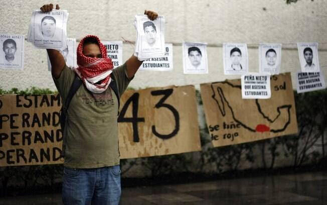 Ativista mostra fotos de alunos desaparecidos durante protesto em frente ao consulado mexicano na Cidade de Guatemala, México (15/10)