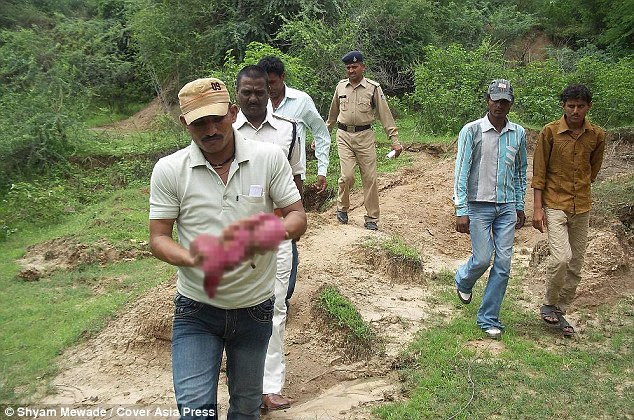 A policeman carries the baby girl from the forest where she was found. She was taken to a local government hospital where doctors battled to save her life
