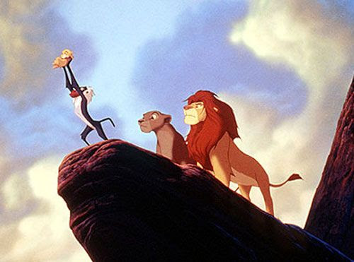 With Mufasa and Sarabi watching, Rafiki presents Simba to residents of the Pride Lands in THE LION KING.