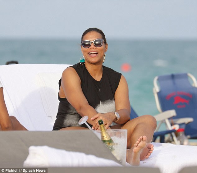 Casual chic: She covered up in a long black tank top under which she wore a blue swimsuit, completing the look with dark shades, large hoop earrings, and a silver watch