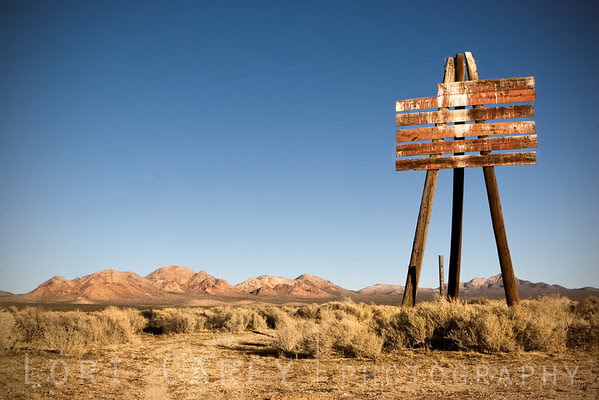 Appears to be an old blank signpost standing tall on three legs near the old gunnery range at Cuddeback Lake in the Mojave Desert, California.