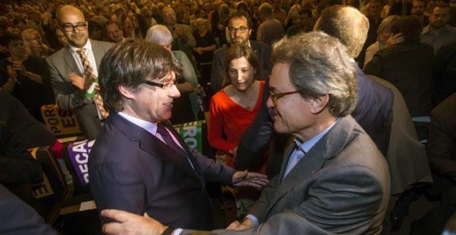 El presidente de la Generalitat Carles Puigdemont, saluda al expresidente Artur Mas en presencia de la presidenta del parlamento catalán, Carme Forcadell. - EFE