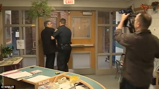 William Baer gets ushered out of a school board meeting in May 2014 by Lt. James Leach, who was then police chief of Gilford, New Hampshire.