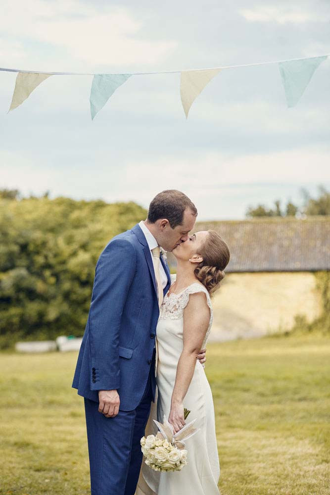 bride and groom kiss under bunting, Great Wilbrham, Cambridgeshire - www.helloromance.co.uk
