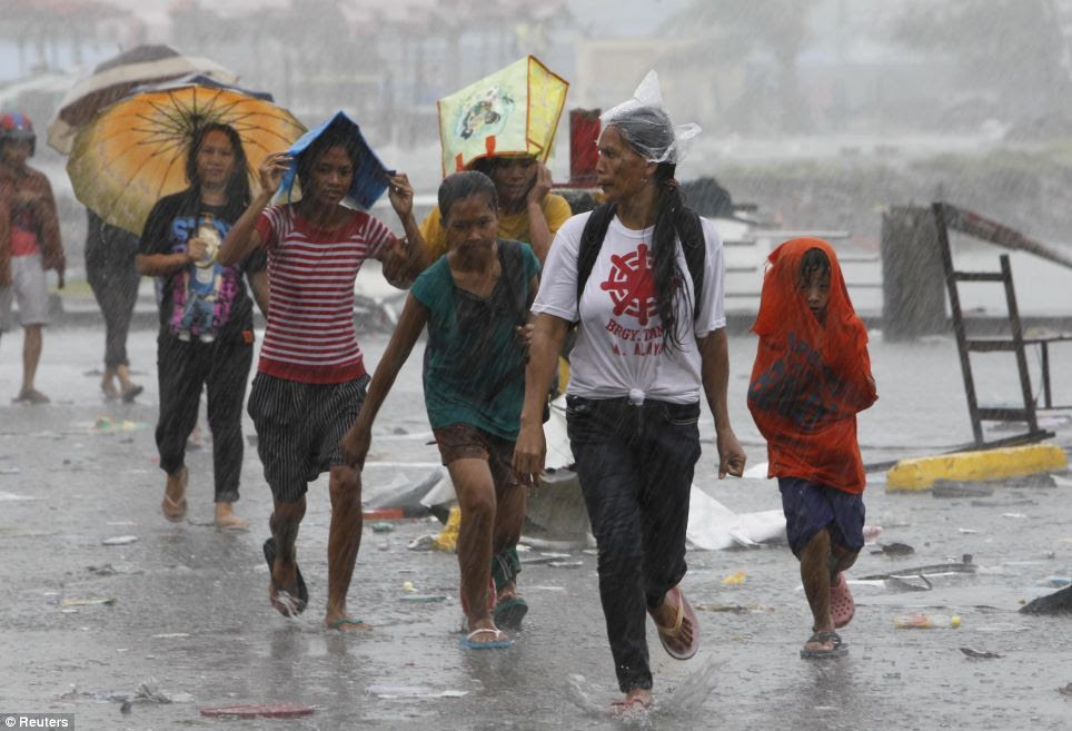 Survivors walk towards the evacuation center to get relief goods after super Typhoon Haiyan battered Tacloban city, central Philippines