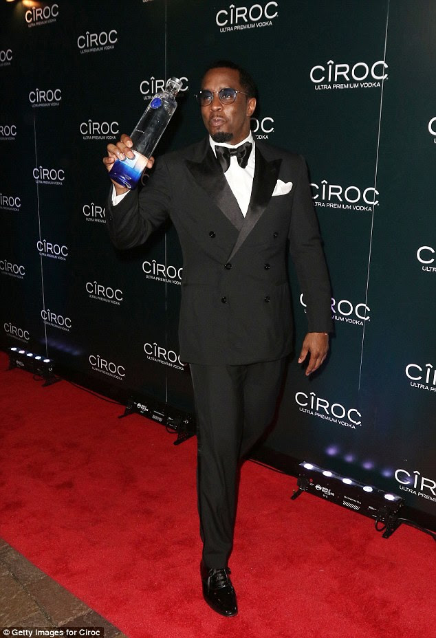 Man of the moment:Diddy looked incredibly suave in a tuxedo while he sported a pair of sunglasses while clutching a bottle of the drink of the evening - Ciroc vodka